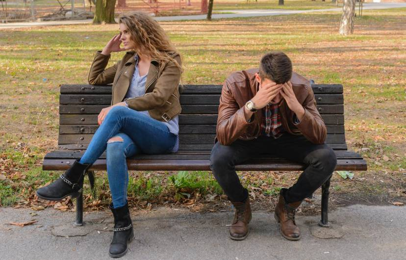 couple sitting on a bench after fight