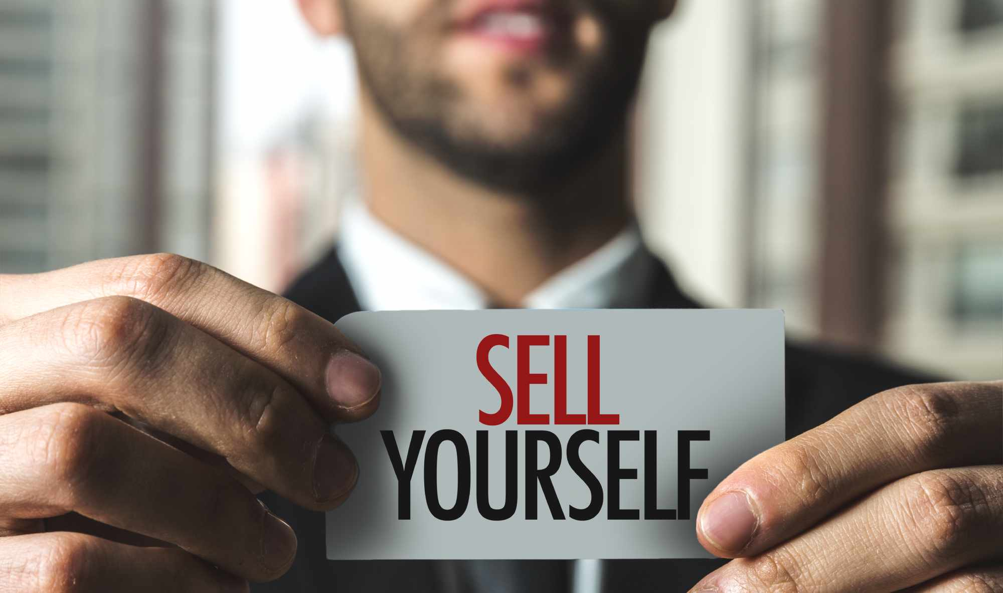 "businessman holding ""sell yourself"" card"