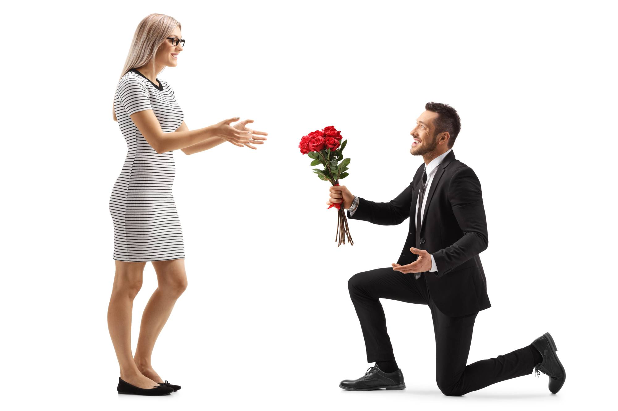 man kneels with red bouquet in front of blonde woman
