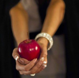 woman holding red apple of manipulation