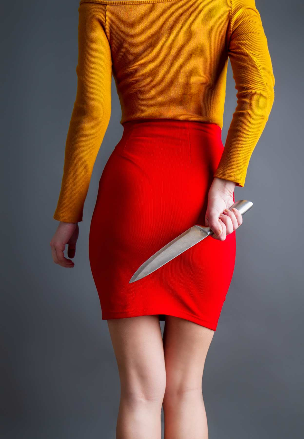 woman in a red skirt holds a knife behind her back