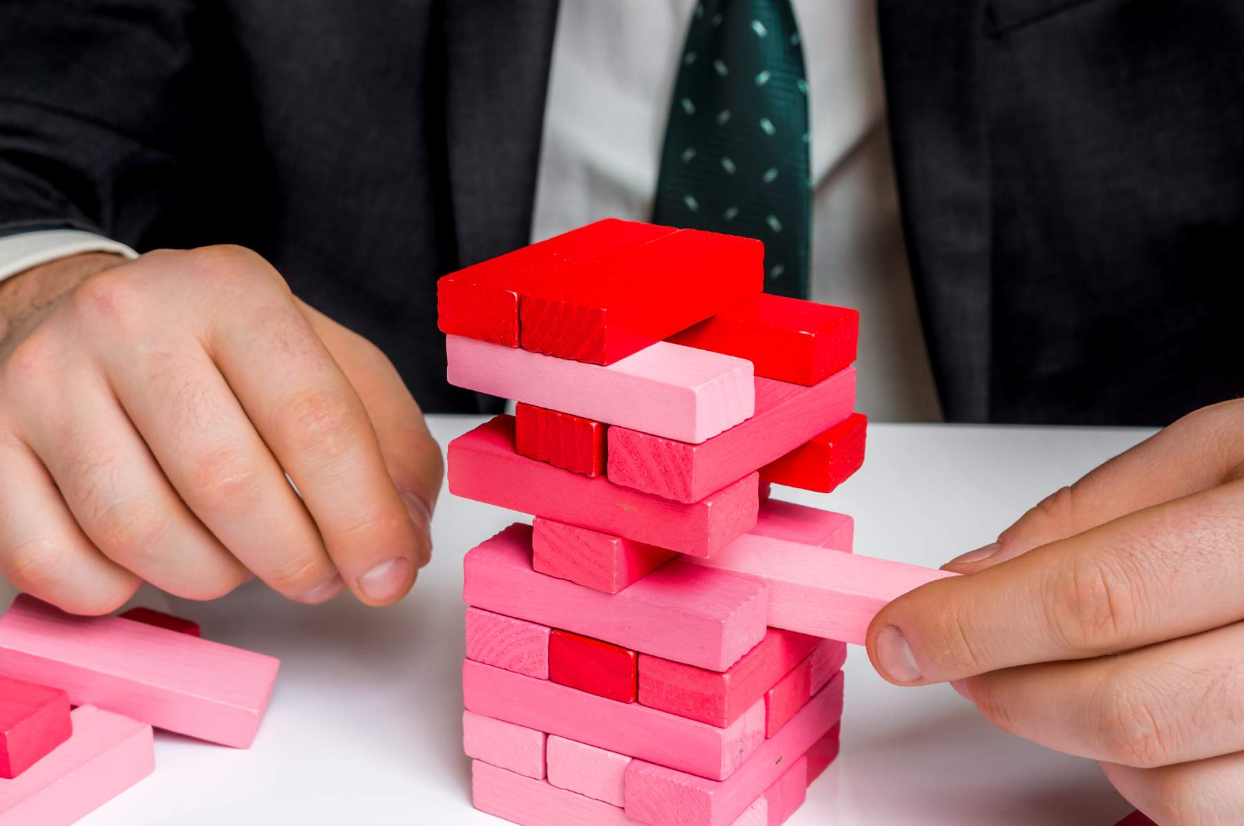 Successful businessman builds big tower with jenga bricks - planning risk and strategy in business