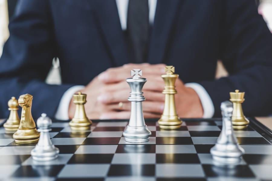 businessman standing in front of a chessboard