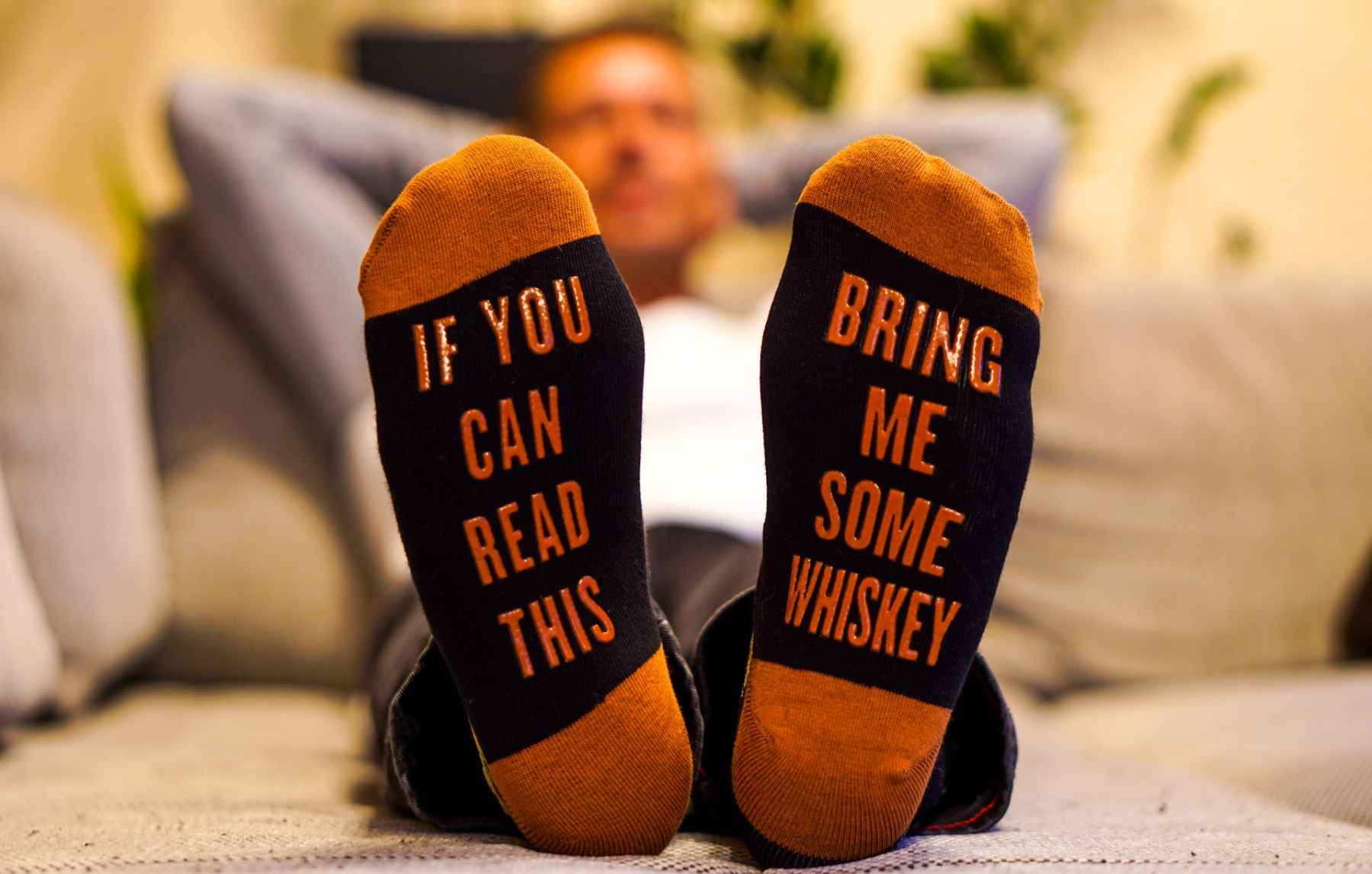 """man chills on couch with socks saying """"bring me some whiskey"""""""
