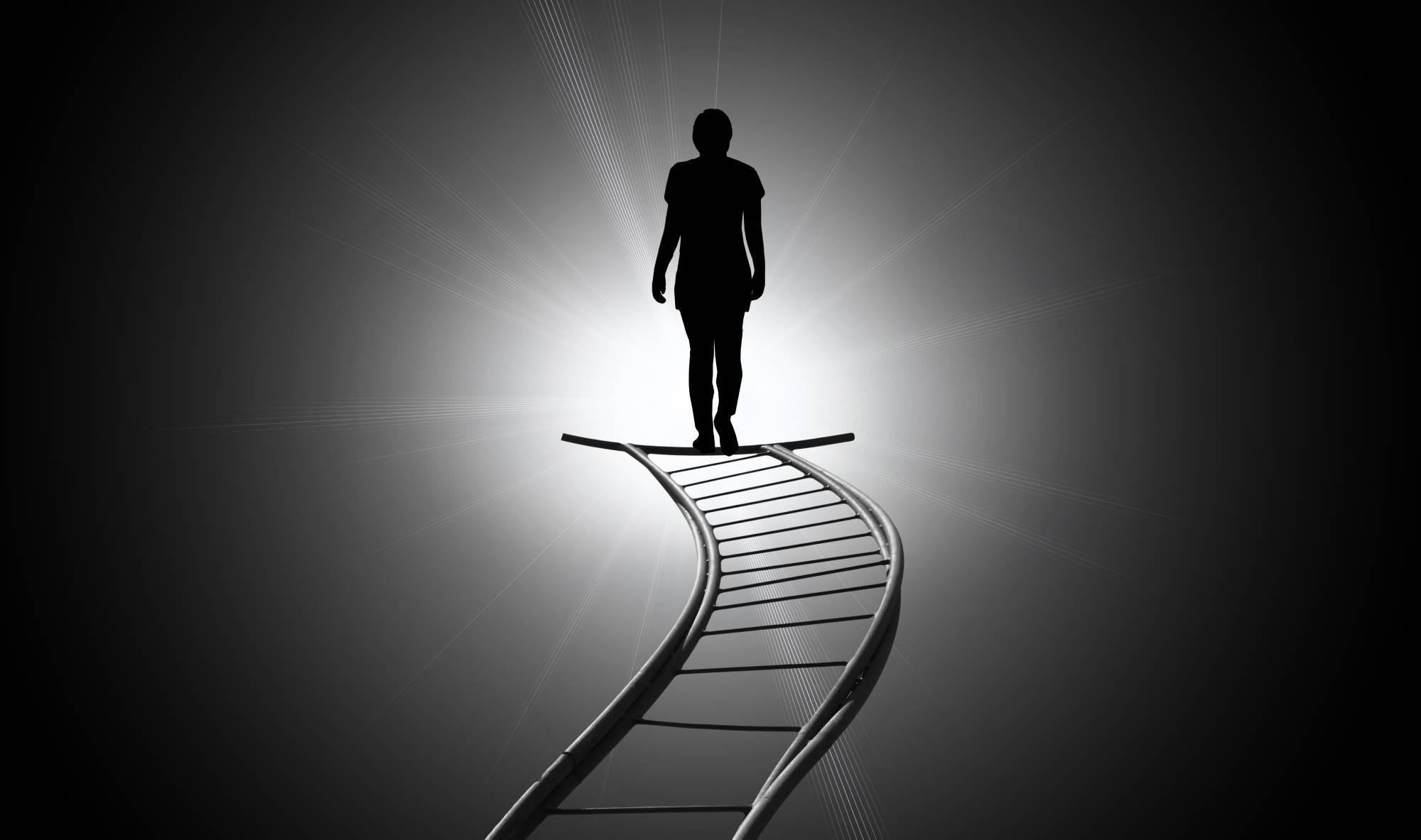 a man walks a staircase towards the sun