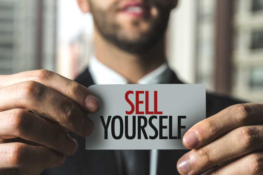 businessman holding sell yourself card