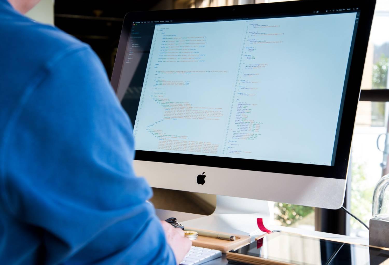 man coding on his computer