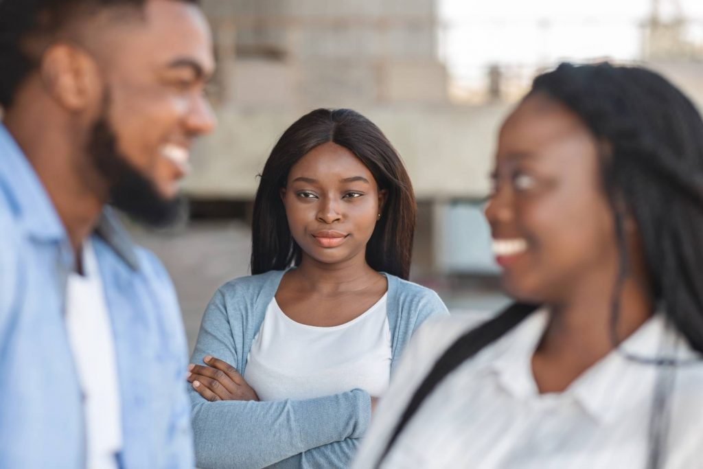 woman watches while a girl flirts with her boyfriend